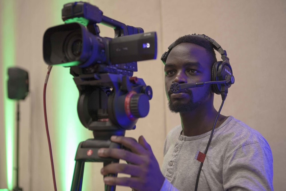 Edgar, one of ADMA students, setting up the Canon XF105, wearing a comms headset to communicate with the technical director