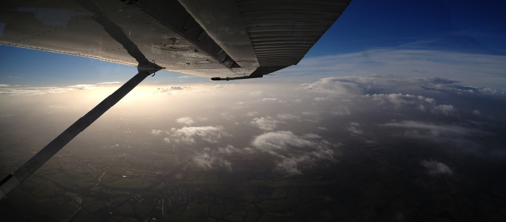 The view from above the clouds over Oxfordshire, from the backseat of a Cessna 182T.
