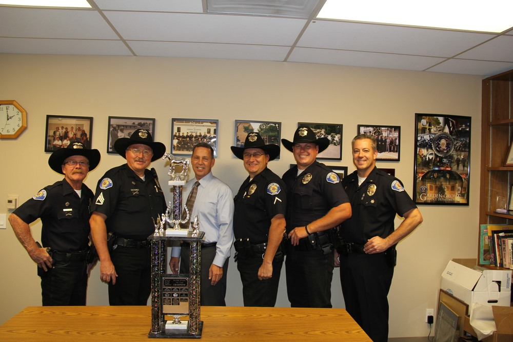 The Garden Grove team presents the trophy to Chief Kevin Raney