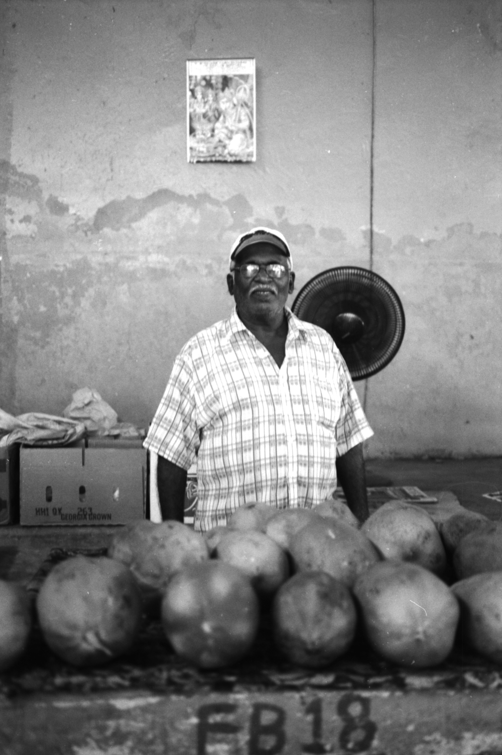 Local selling coconuts at the towns market. It amazed me at how he asked for his picture to be taken, he never asked what was going to be done with the image or anything like that. He was just happy to have his picture taken even though he would mostly never see the outcome of it.