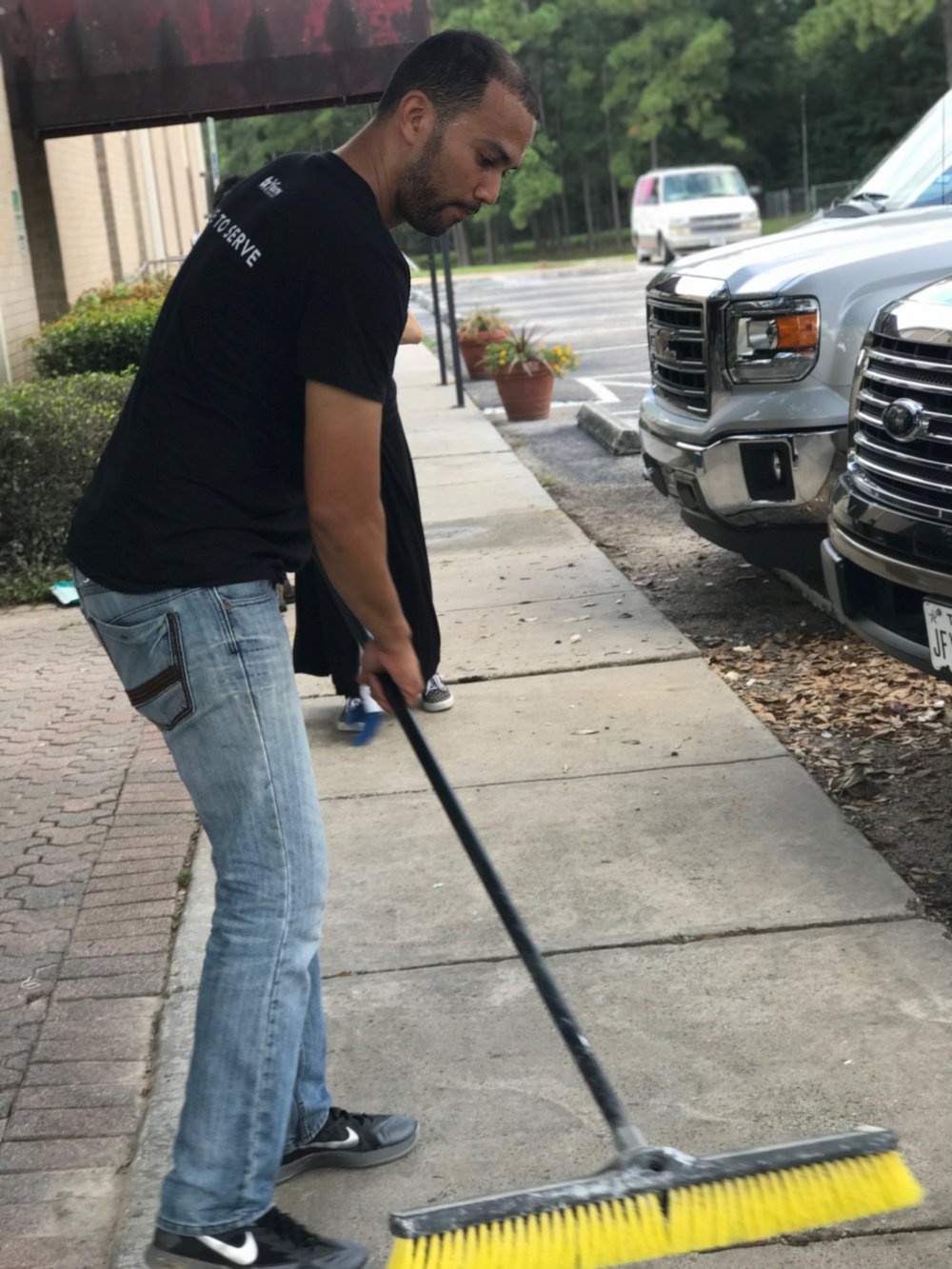 Chris Chung sweeping school grounds.