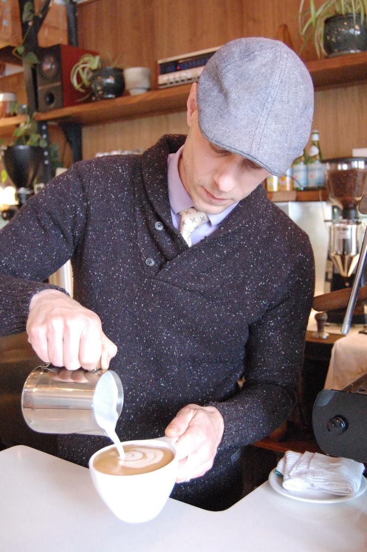 Tyree slinging lattes at the Alberta Cafe