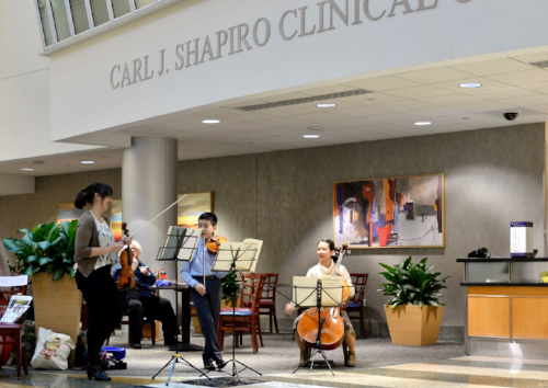 Gabby with students from Boston Youth Symphony Orchestra playing in the Shapiro Center at Beth Israel Hospital