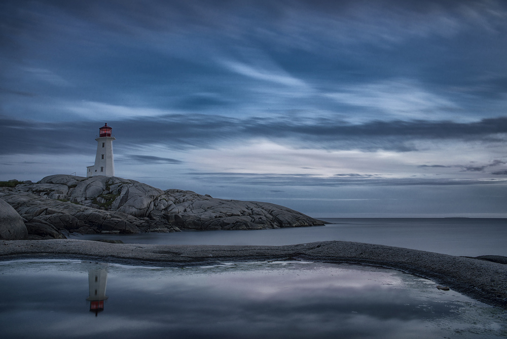 Peggy's Cove lighthouse sits out on a point of rocks that goes out into the Atlantic Ocean. The winds often blow strong and the lighthouse sits high on a rock formation. I wanted to position the lighthouse on the rocks and show the skies that blow across the exposed coastline.