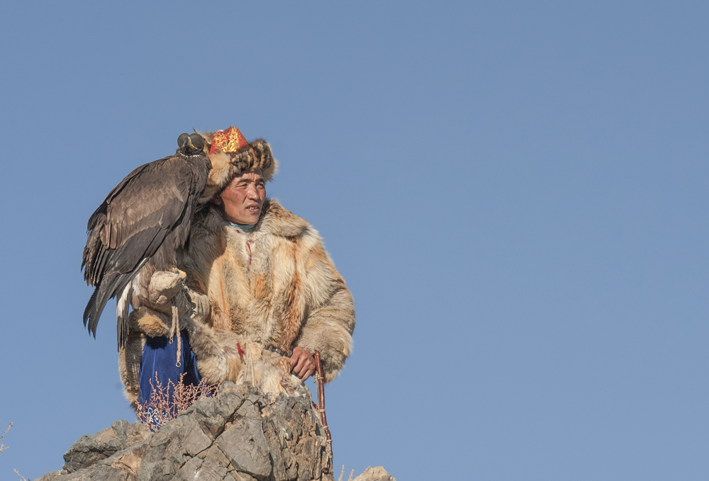 Kazakh Eagle Hunter sits on top of a cliff with his Golden Eagle