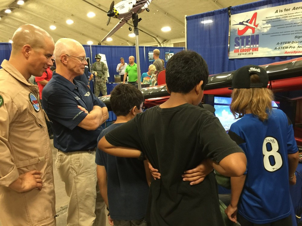 """AG-1 A-STEM Marketing expert Rich Kenney and retired USMC fighter pilot Leo Melendez monitored progress as students tried their hand at flying a simulator """"Blue Angels"""" F/A-18 Hornet."""