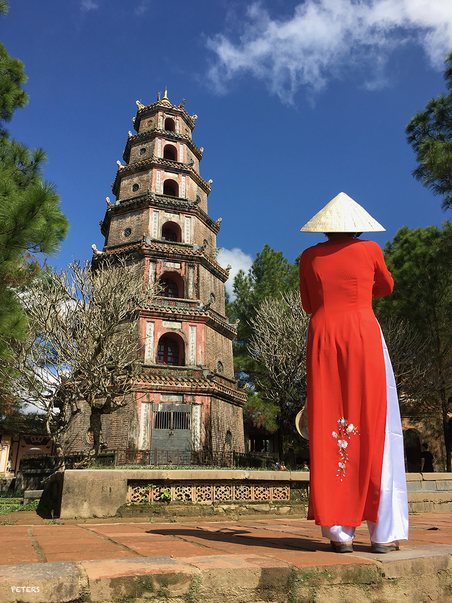 A woman in a traditional Vietnamese Ao Dai stands in front of the seven-tiered Thien Mu pagoda, a historic pagoda on the banks of the Perfume River in the Vietnamese city of Hue.