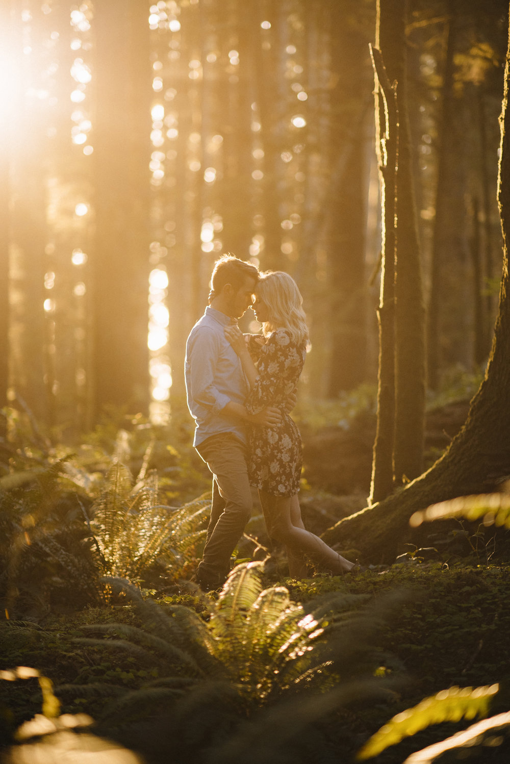 A married couple snuggles in the forest on Oregon Coast.  Adventurous couples photography by Colby Moore.