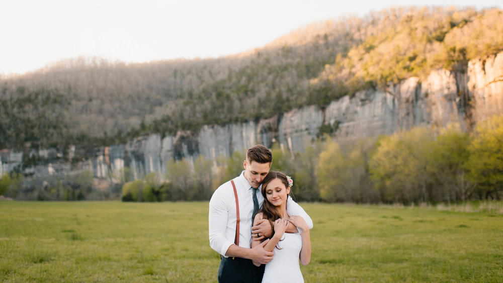 A bride and groom snuggle in front of the towering bluffs at Steele Creek after their Buffalo River Wedding with Arkansas Adventure Destination Photographer Colby and Jess