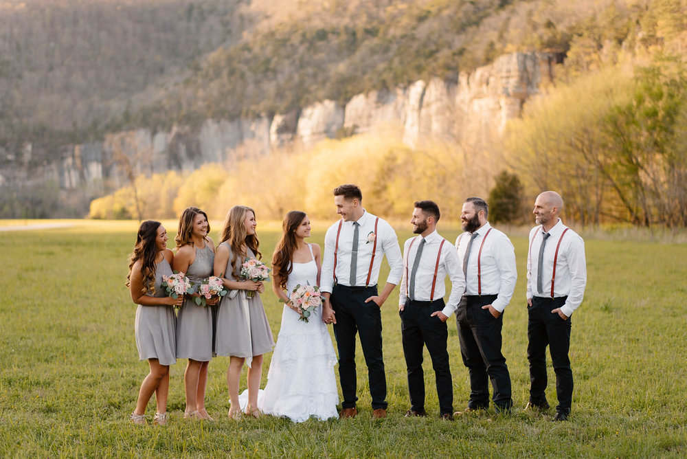 A bridal party stands in front of the bluffs after their Buffalo River Wedding with Arkansas Adventure Destination Photographer Colby and Jess