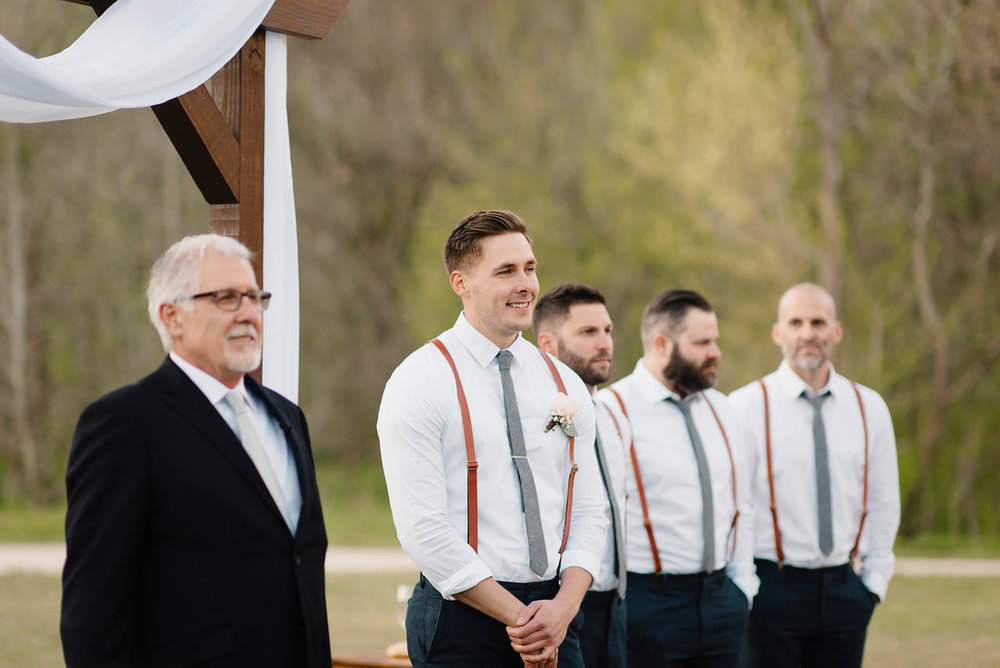 A groom watches his bride walk down the aisle during their Outdoor Buffalo River Wedding by Arkansas Adventure Destination Elopement Photographer Colby and Jess