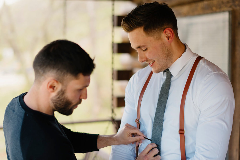 A groom's brother helps him get ready for his Buffalo River Wedding by Ozarks Adventure Destination Elopement Photographers Colby and Jess