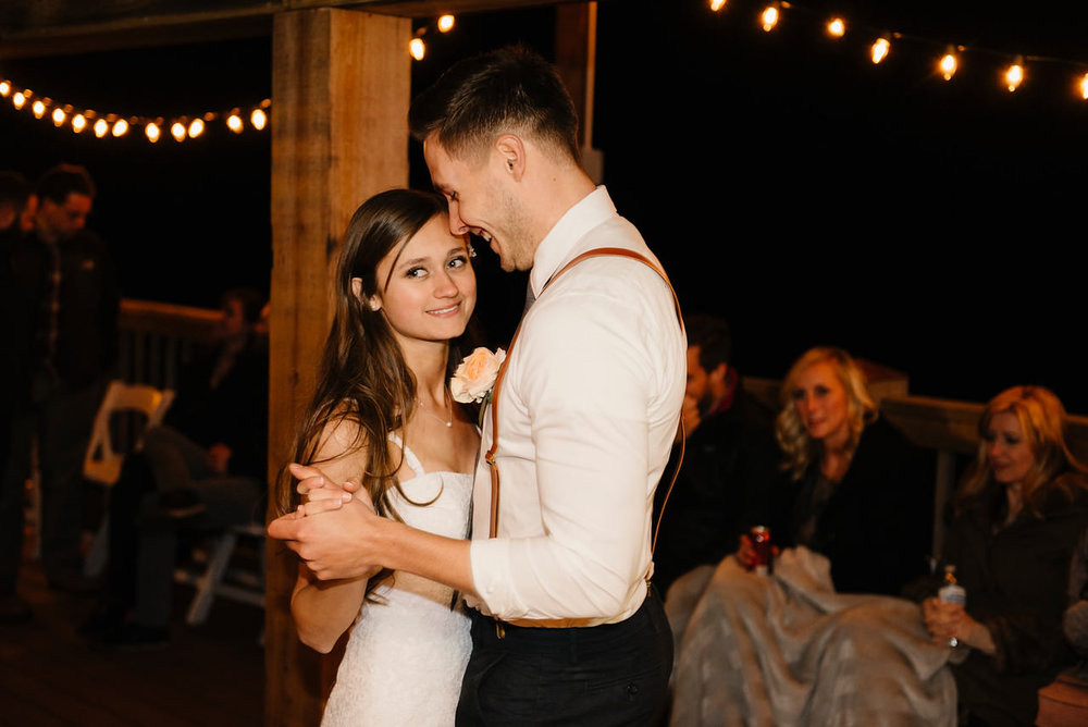 A bride smiles as she dances with her groom after being married at Steele Creek Buffalo River with Arkansas Adventure Destination Photographer Colby and Jess