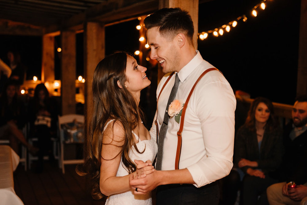 A bride and groom dance under lights after their Buffalo River Wedding by Arkansas Adventure Destination Photographer Colby and Jess