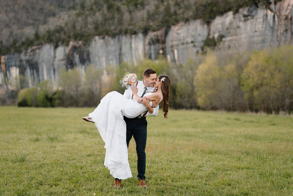 A groom picks up his bride at Steele Creek Buffalo River with Arkansas Adventure Destination Photographer Colby and Jess