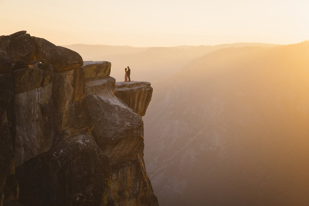 Romantic couple on cliff of taft point at sunset by Yosemite Elopement Photographer Colby and Jess colbyandjess.com