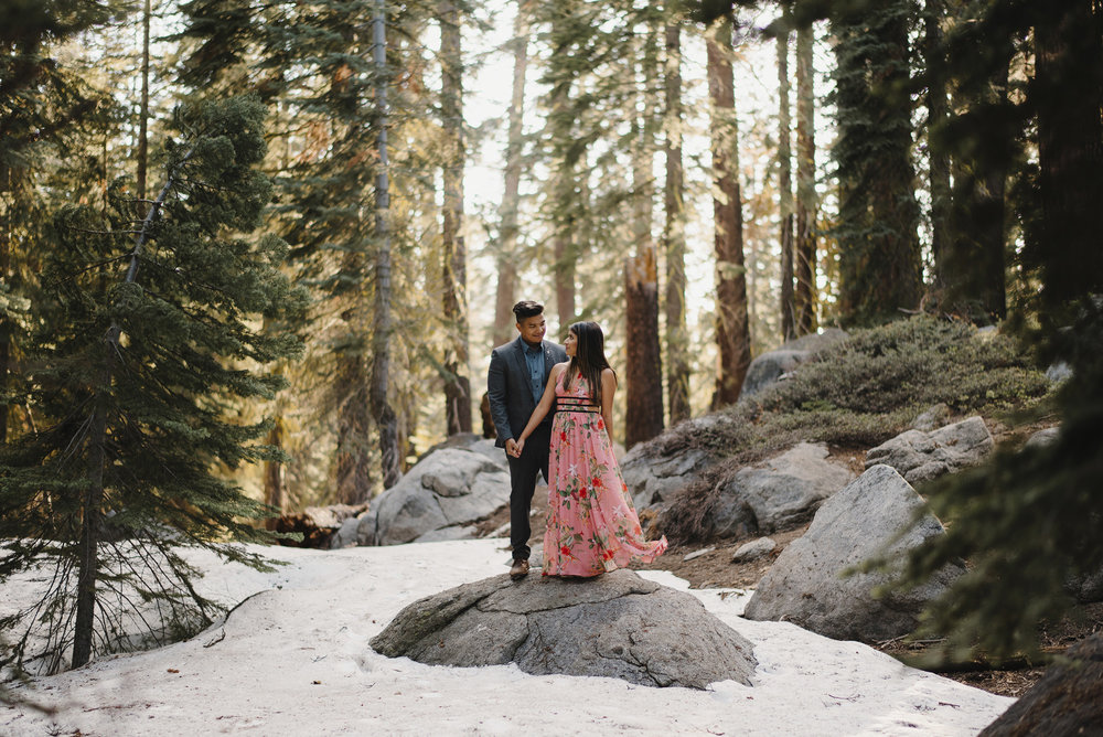 Engaged couple smile at each other along snow covered Taft Point Trail in Yosemite