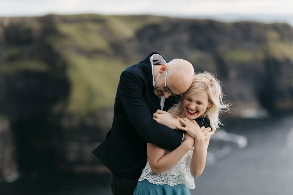Man and woman laugh together during adventure photography session by cliffs of moher elopement photographer Colby and Jess