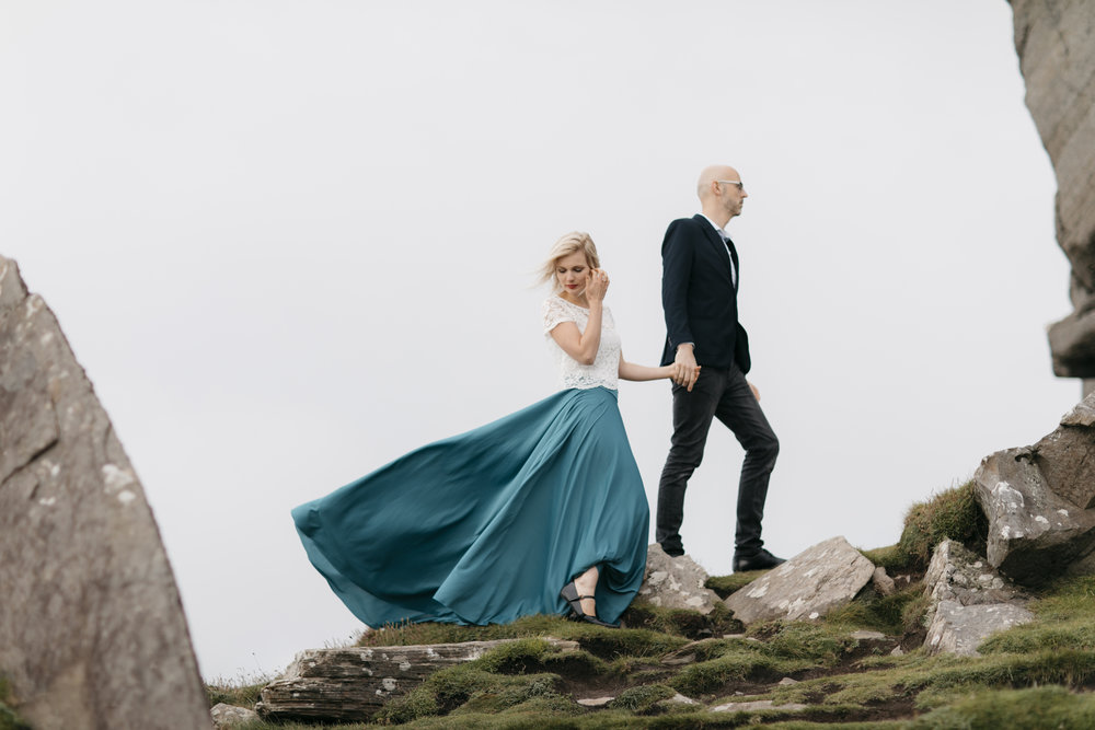 Couple walk on rocks at Cliffs of Moher during adventure photography session by ireland elopement photographers Colby and Jess