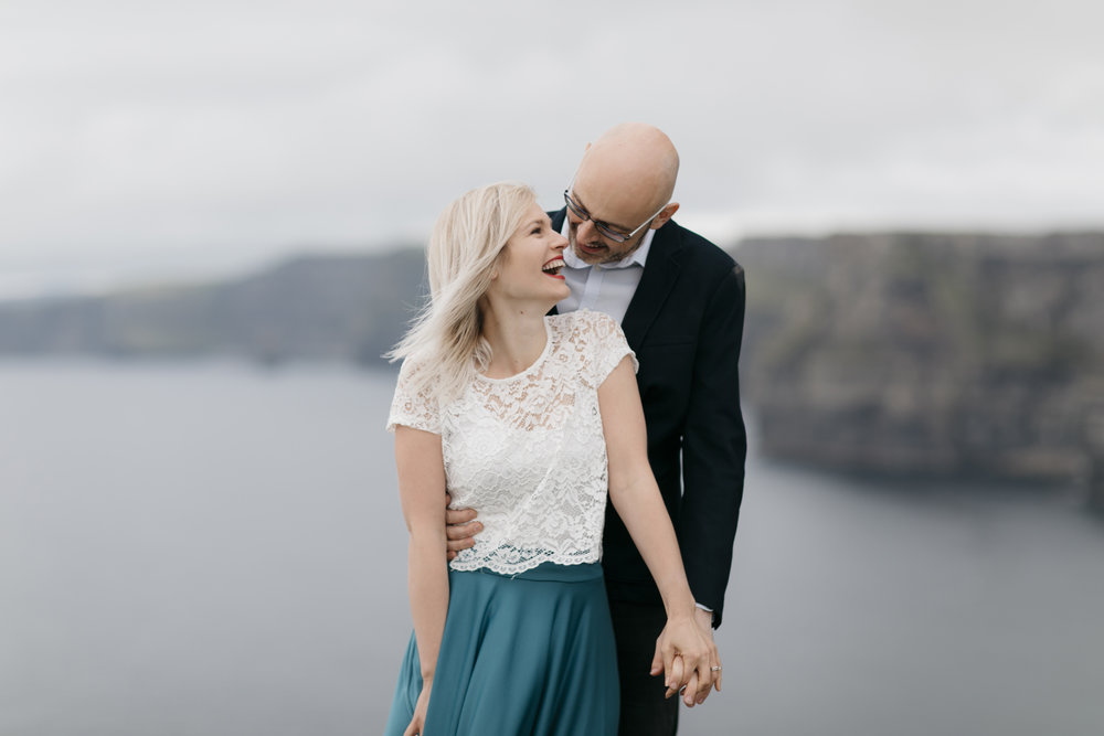 Annie laughs at joke made by Matt during their adventure photography session done at Cliffs of Moher by Ireland Elopement Photographers Colby and Jess