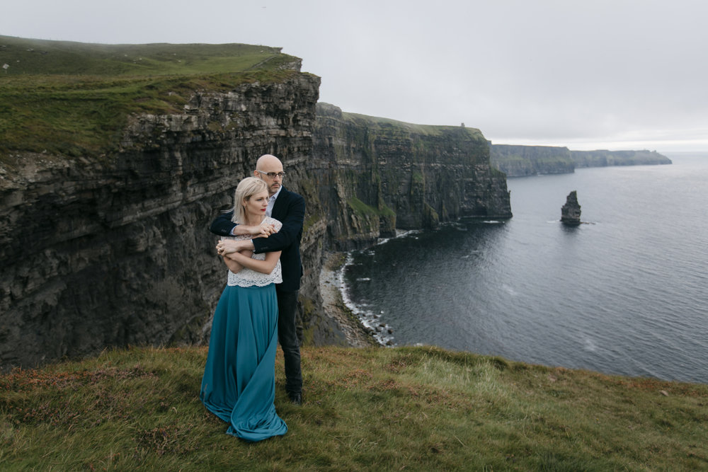 Married couple embraces at Cliffs of Moher during their epic photography session by Ireland Elopement photographer Colby and Jess