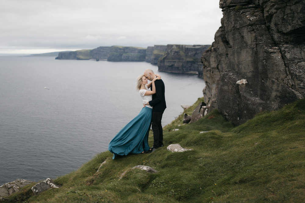 A beautiful couple clings to each other on the Cliffs of Moher during adventure photography session by Ireland Elopement photographers Colby and Jess