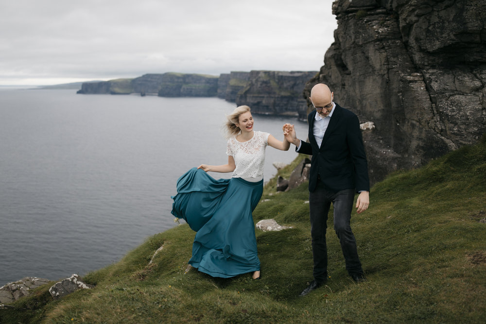 A man leads his wife along Cliffs of Moher during anniversary photography session by adventure wedding photographer colby and jess