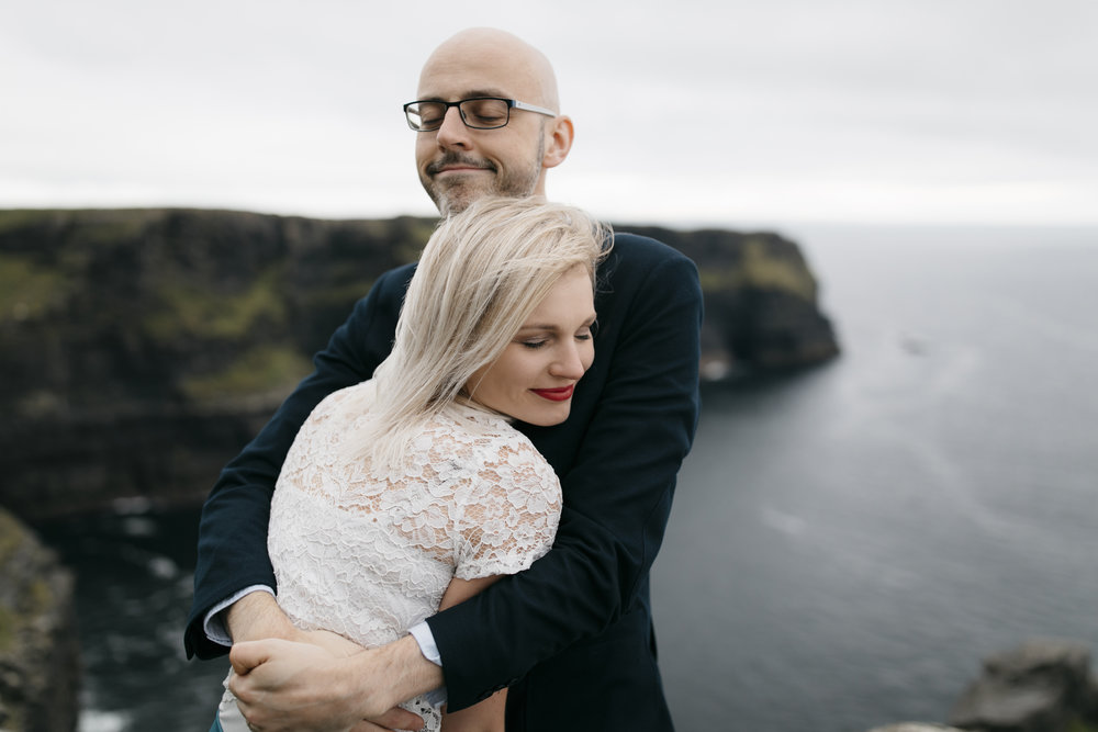 An adventurous couple hold each other tight at the Cliffs of Moher during anniversary adventure session by Ireland Elopement Photographers Colby and Jess