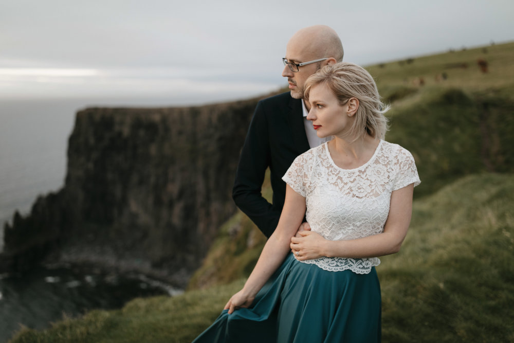 Looking out to the sea, an adventurous couple stand at the Cliffs of Moher while being photographed by Ireland Elopement Photographers Colby and Jess
