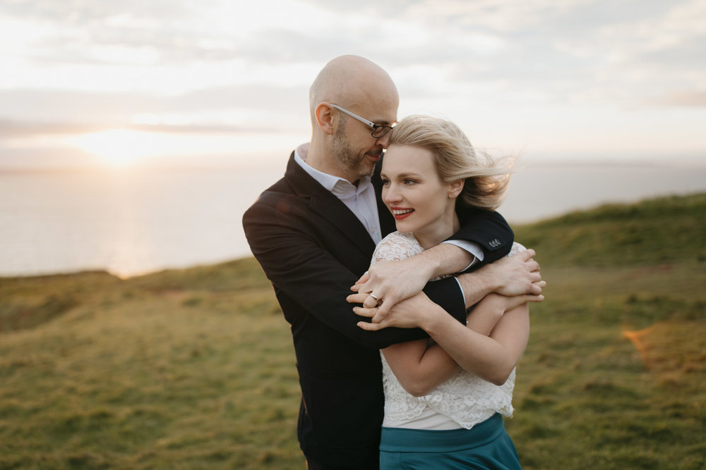 a couple snuggles at the cliffs of moher during adventure elopement in ireland