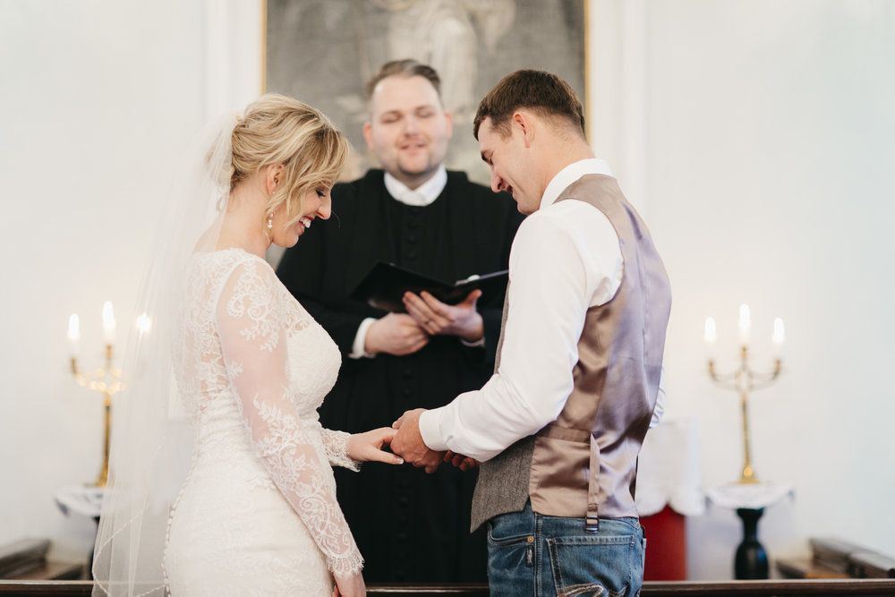 Groom slips the ring on his bride's finger during elopement ceremony in Hvalsneskirkja Church with their Iceland wedding photographers Colby and Jess.