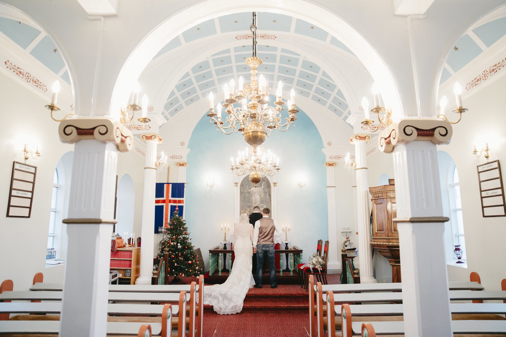 An engaged couple walks to the front of the church Hvalsneskirkja to elope in Iceland with their adventure elopement photographers Colby and Jess.