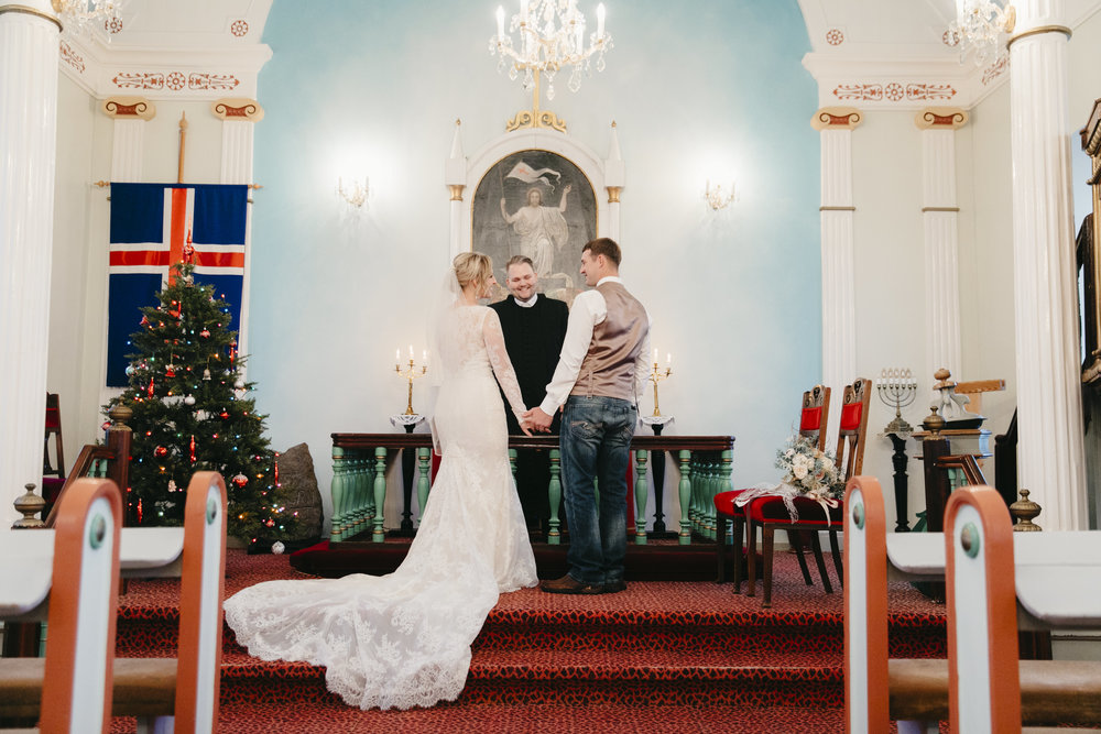 A couple stands in the front of the Hvalsneskirkja Church in Iceland during their Iceland Elopement Wedding by photographers Colby and Jess.