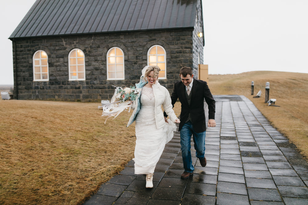 The happy married couple leaves the Hvalsneskirkja Church after finishing elopement ceremony with their Iceland Elopement photographers Colby and Jess, colbyandjess.com