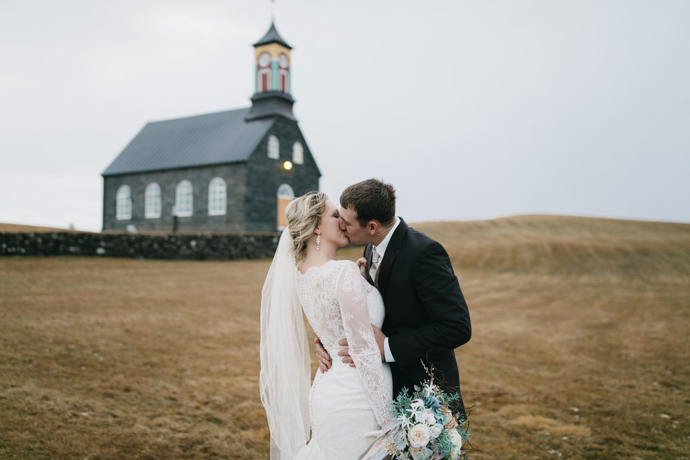 After their wedding in Hvalsneskirkja Church this couple kiss to celebrate with their Iceland Elopement photographers Colby and Jess, colbyandjess.com