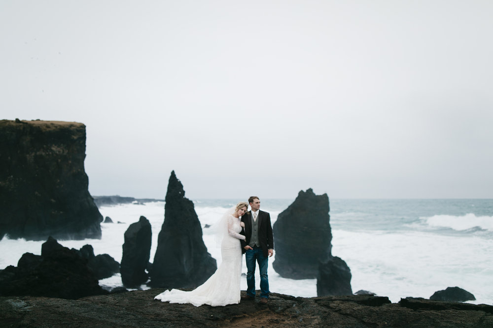 A lovely couple snuggles on the coast of Iceland during their elopement adventure session by photographers Colby and Jess, colbyandjess.com