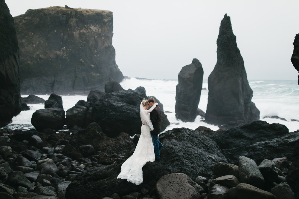 A couple snuggles at Reykjanes peninsula after their adventure elopement in Iceland by destination wedding photographers colby and jess, colbyandjess.com