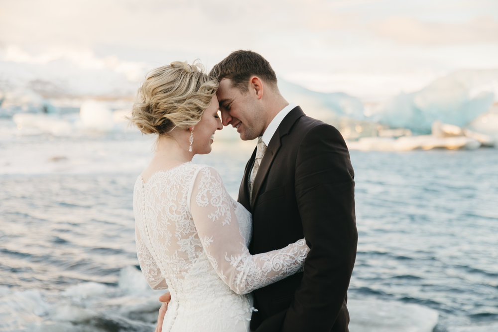 A couple stands next to a glacier during their jokulsarlon elopement with Iceland wedding photographers Colby and Jess.