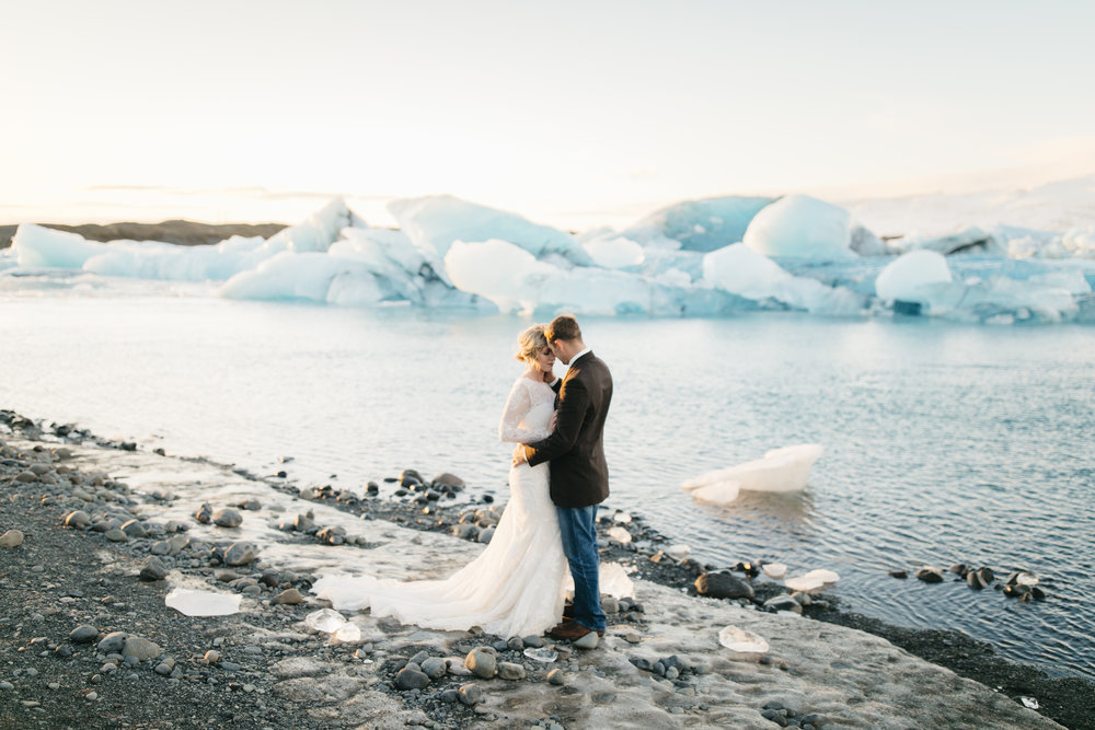 A man embraces his bride beside jokulsarlon glaciers during Iceland Elopement Photography session with Colby and Jess.