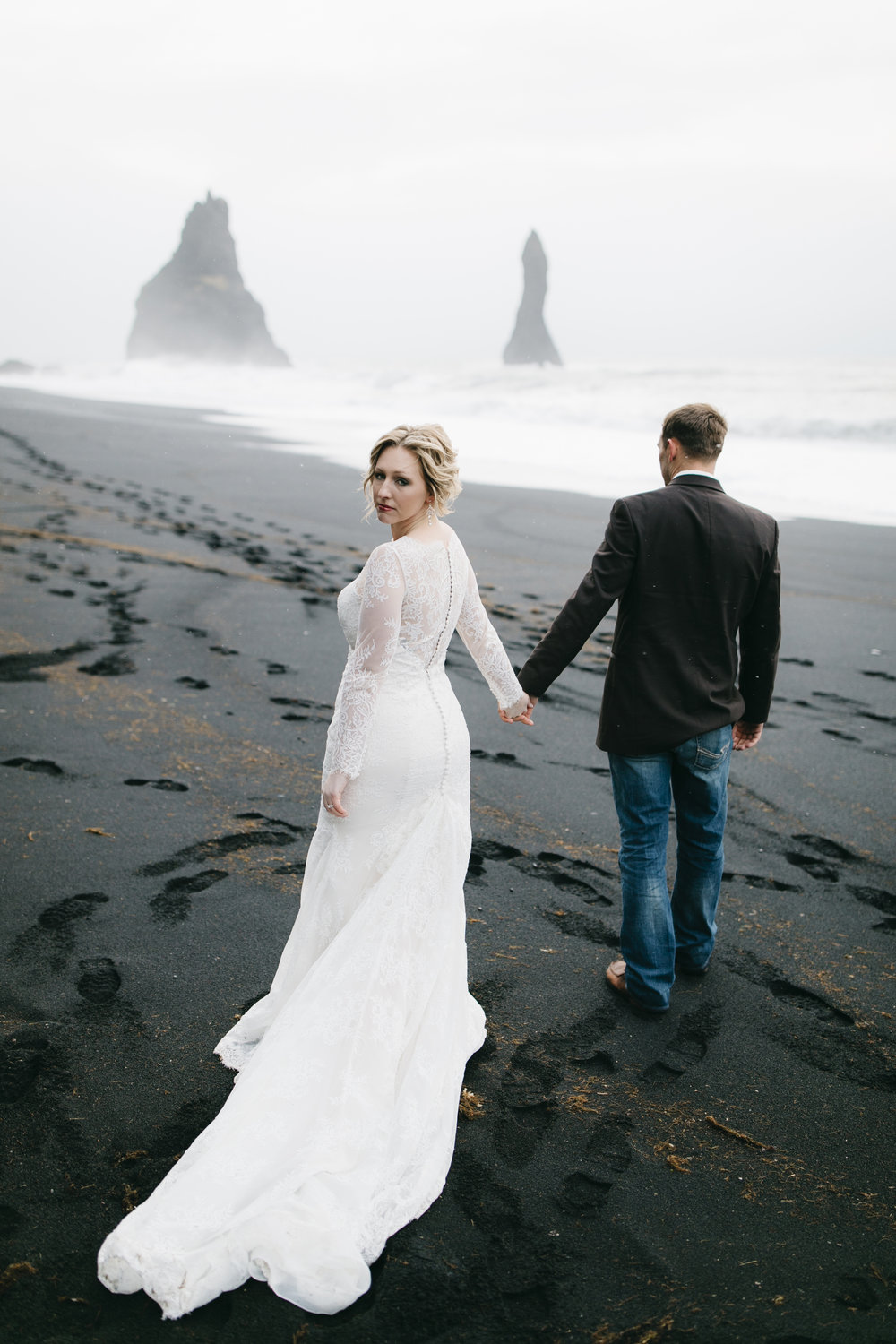 A beautiful bride walks with her groom on a black sand beach in Vik, looking over her shoulder at Iceland Wedding Photographers Colby and Jess, colbyandjess.com