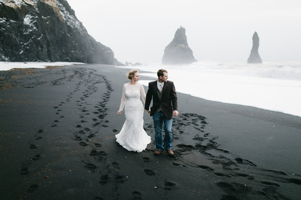 A man and his wife walk along the black sand beaches in Vik after their adventure elopement with Iceland wedding photographers Colby and Jess, colbyandjess.com