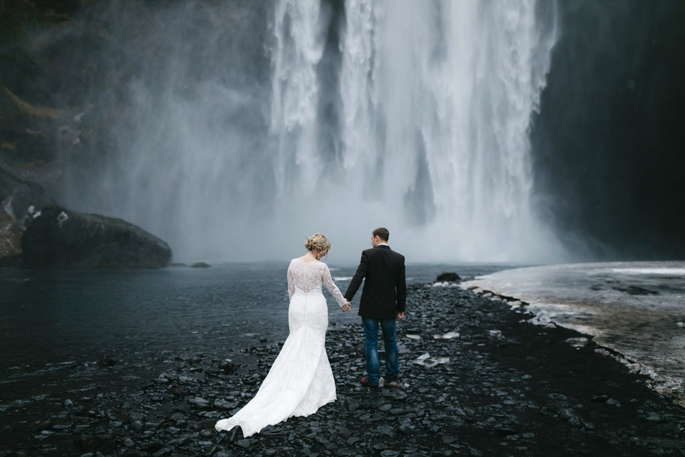 A couple walks to Skogafoss waterfall for their Iceland Elopement photography session with wedding photographers Colby and Jess, colbyandjess.com