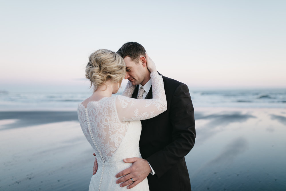 The sun sets on black sand beach during an Iceland Elopement Photography session by Colby and Jess.