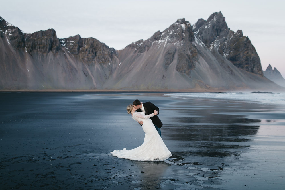Vestrahorn mountain reflects on the black sand beach while couple kisses with Iceland Elopement photographers colby and jess.