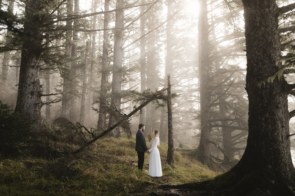 A couple reads their vows in the forest of the Oregon Coast during their adventure elopement with photographers colby and jess.