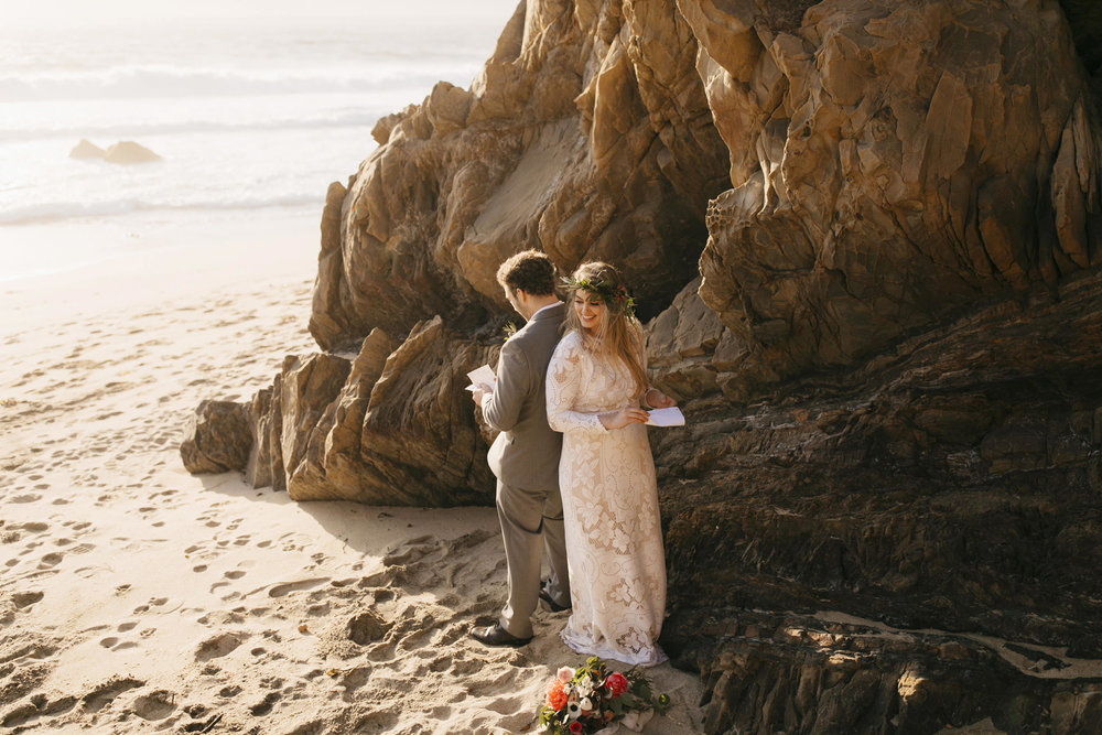 A couple reads their vows on the beach during their Big Sur Elopement by Adventure Destination Elopement Photographers Colby and Jess