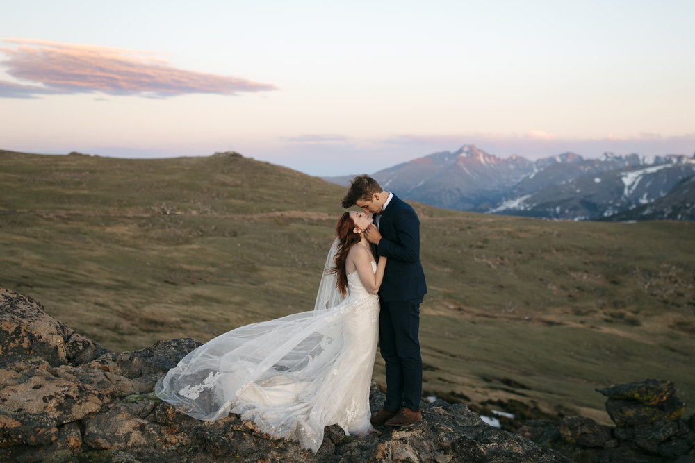 A couple shares a romantic kiss during sunset with their Rocky Mountain National Park Destination Elopement Photographers Colby and Jess