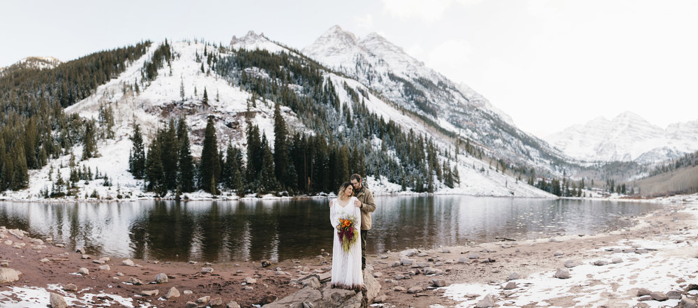 Maroon Bells Destination Elopement Photographers capture a couple standing lakeside after their elopement ceremony.