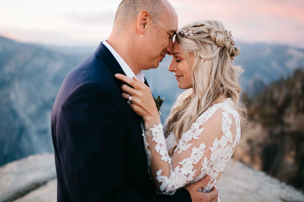 A bride and groom share a romantic embrace at Taft Point with Yosemite Destination Elopement Photographers Colby and Jess.