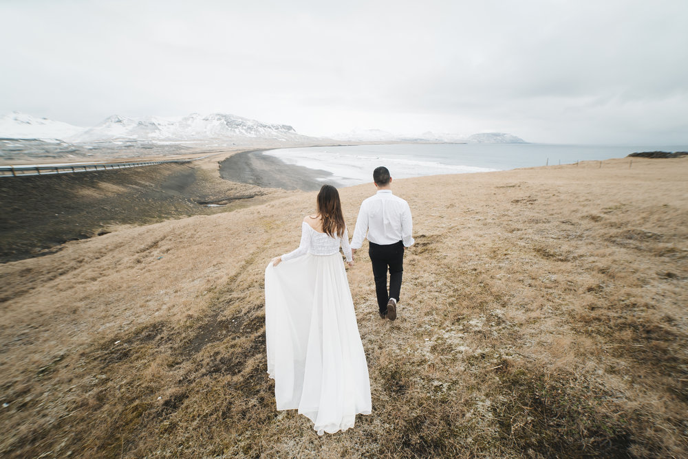 A groom leads his bride on an adventure during their Iceland Destination Elopement with Photographers Colby and Jess.